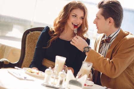 Photo pour The man, a beautiful brunette with brown eyes, light brown suit and bow tie and red-haired young woman with brown eyes, wearing a black dress, spend time together over a cup of coffee in summer cafe outdoors. - image libre de droit