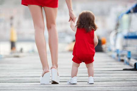 Photo for beautiful mother is walking on the pier with her little baby girl daughter with first steps. First steps. mother and child. mother holding child's hands supporting by learning to walk - Royalty Free Image