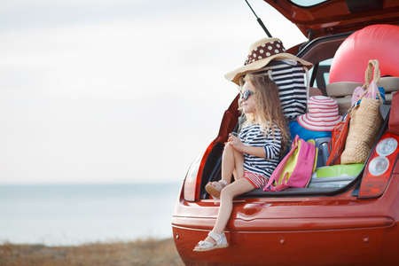 Photo for A little girl, a brunette with long curly hair, dressed in a striped sailor shirt, dark sun glasses, and a journey to the sea, sits in the trunk of the red car with clothes, suitcases and bags - Royalty Free Image