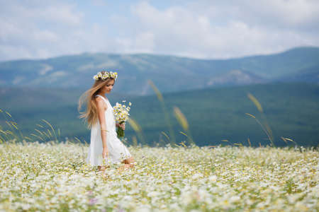 Young beautiful woman brunette with long straight hair, holding a bouquet of beautiful flowers field daisies, dressed in a white sleeveless dress, her head wears a wreath of white flowers field of daisies, walking alone in a flowery field in summer