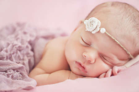 Foto de Close-up portrait of a beautiful sleeping baby.Happy carefree sleep little baby with wreath on head in warm pink bed, the child was put under the cheek stick, pink soft skin and fluffy hair, covered with a pink blanket - Imagen libre de derechos