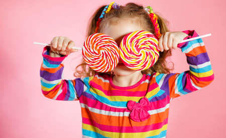 Photo for Funny little girl with long, curly red hair, bright ribbons tied into two tails, a sweet smile, wearing a bright dress with a red bow on the chest, posing in Studio on pink background holding two big colorful Lollipop - Royalty Free Image
