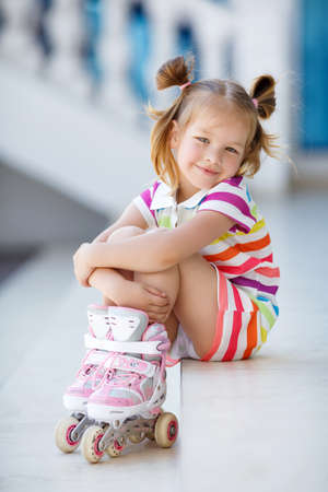 Photo for Cute little red-haired girl with hair in two ponytails, grey eyes and sweet smile, dressed in a multicolored striped dress with short sleeves, learning to roller skate in the city in the fresh air in the summer - Royalty Free Image