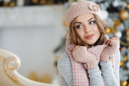 Red-haired beautiful young woman with blue eyes and curly long hair, in a beige knitted hat, scarf and gloves, beautiful makeup and large black eyelashes, purple nail Polish, posing in Studio on light background ornate Christmas tree with yellow balls