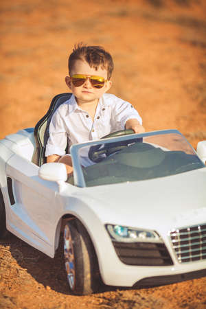 Foto de The little boy, the driver with a fashionable hairstyle, brown hair, wears mirrored, sun glasses, gold, wearing a white fashionable shirt, running a child's electric car, a white convertible, posing outdoors in the summer on the rocky coast of the ocean - Imagen libre de derechos