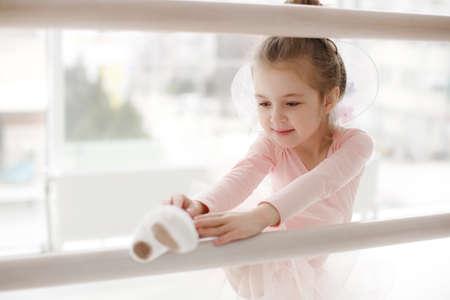 Photo pour Little ballet girl in ballet studio. Little ballerina girl in a pink tutu. Adorable child dancing classical ballet in a white studio. Children dance.Young gifted dancer in a class. Preschool kid taking art lessons. Little Ballet Star - image libre de droit