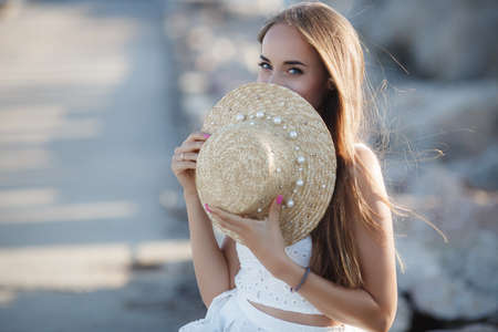 Photo for Beautiful brunette sitting on the rocks.Sexy brunette girl posing alone on the beach in the evening.Young pretty hot sexy attractive girl relaxing in in a in a white dress and hat on stones with blue sea and sky on background.Summer Vacation Concept. - Royalty Free Image