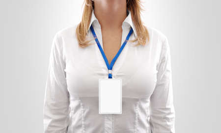 Foto de Woman wear blank white vertical badge mockup, stand isolated. Name tag on neck and chest. Person identity label. Women in shirt uniform with empty id card mock up.  Bussinesswoman pass design. - Imagen libre de derechos