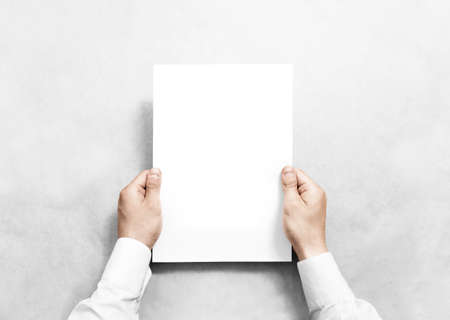 Photo pour Hand holding white blank paper sheet mockup, isolated. Arm in shirt hold clear brochure template mock up. Leaflet document surface design. Simple pure print display show. Reading contract agreement. - image libre de droit