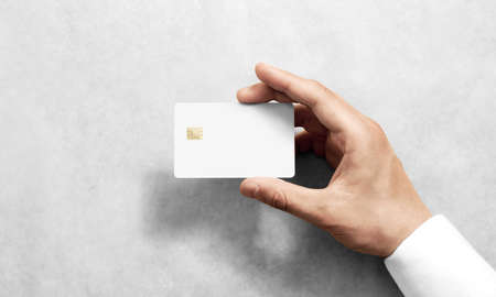 Photo pour Hand holding blank white credit card mockup with rounded corners. Plain creditcard mock up template with electronic chip holding arm. Plastic bank-card display front design. Business branding. - image libre de droit