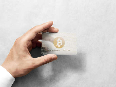Foto de Hand holding bitcoin card template with embossed gold logo mockup. Plain plastic cryptocurrency payment-card display front view, design mock up. Electronic mining template. - Imagen libre de derechos