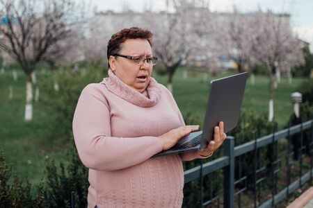 Foto de woman sweeping in glasses uses her laptop, she's scared, she saw what she did not need to see, dressed in a pink sweater and in jeans, outdoors - Imagen libre de derechos