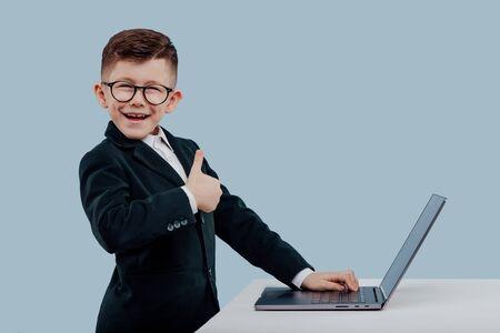 Photo pour thumb up, positive schoolboy in suit and glasses - image libre de droit