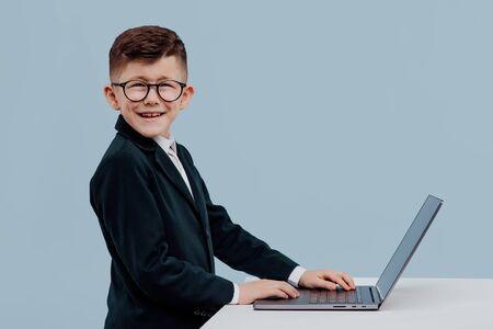 Photo pour Cheerful little manger using laptop blue background - image libre de droit