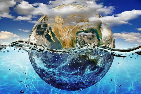 Foto de Earth is immersed in water, among the clouds against the sky. - Imagen libre de derechos
