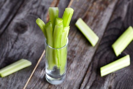 Photo for Cutted celery sticks in small glass on wood background. Snack for buffalo wings - Royalty Free Image