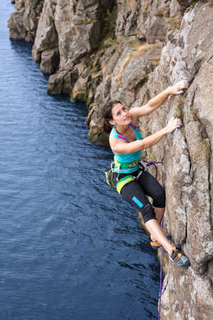 Female extreme climber conquers steep rock over the impressive rocky beach