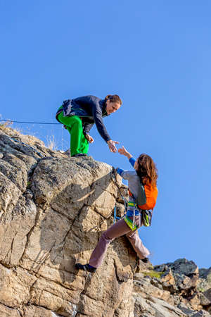 Foto de Climber helps her partner to rich the summit Two female climbers, one drags the hand of another. Deep blue sky on the background - Imagen libre de derechos