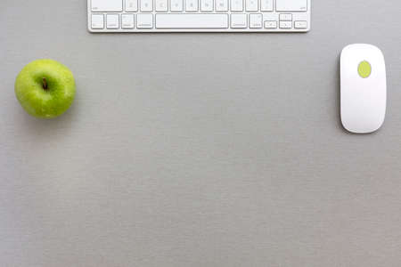 Photo for Working space in grey-green Creative office style composition with green apple and computer keyboard and mouse located on grey wooden desk. Top view - Royalty Free Image