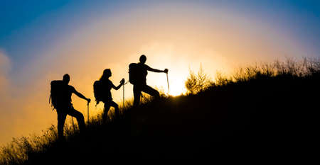 Climbers on grassy hill Family three people silhouette walking up steep grassy hill majestic sunrise and blue sky background