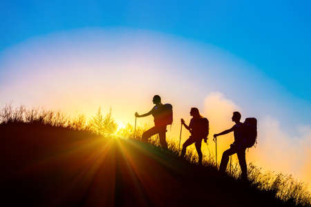 Foto de Group of people silhouettes walking toward mountain summit with backpacks hiking trekking gear meeting uprising sun sunbeams and blue sky of background - Imagen libre de derechos