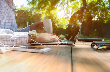 Photo pour Smart casual dressed person working on computer drinking coffee mug sitting at rough natural wooden desk outdoor with green tree and sun on background - image libre de droit
