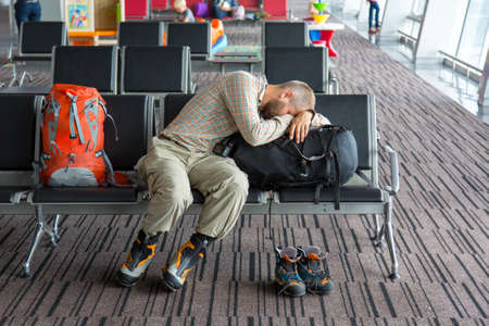 Photo pour Body of male on foreground sleeping on his luggage lying in chair other people miscellaneous actions on background terminal interior with large windows - image libre de droit