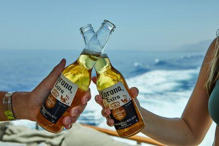 Foto de Eilat, Israel - July 13, 2019: Male and female hands holding a Corona beer on a luxury yacht on the Red Sea. - Imagen libre de derechos