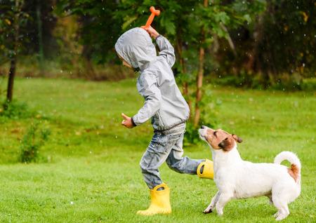 Photo pour Kid boy wearing waterproof coat playing with a dog - image libre de droit