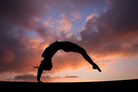 Photo pour back handspring of female gymnast in sunset sky - image libre de droit