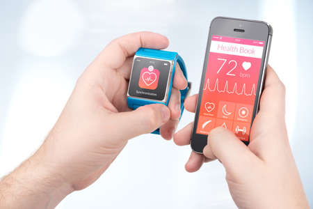 Foto de Data synchronization of health book between smartwatch and smartphone in male hands - Imagen libre de derechos