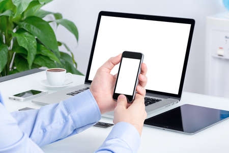 Foto de Male hands using smartphone mockup with blank screen at the office desk with an open laptop mockup and tablet computer. All devices in full focus. For responsive design presentation. - Imagen libre de derechos