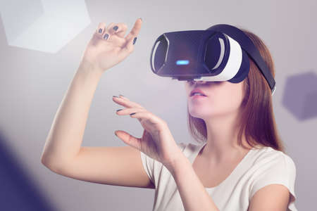 Photo pour Woman in VR headset looking up and trying to touch objects in virtual reality. VR is a computer technology that simulates a physical presence and allows the user to interact with environment. - image libre de droit