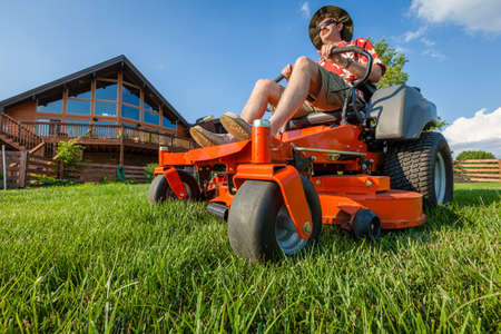 Photo pour A man is mowing backyard on a riding zero turn lawnmower - image libre de droit