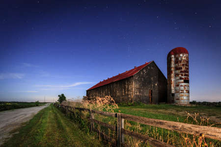 Photo pour Scenic nighttime image of an old farm barn and a country road in moonlight - image libre de droit
