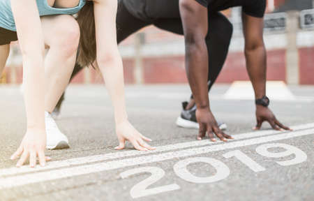 Foto de young couple afro-american man and european woman run together. A loving couple is run, engaged in sports, family values. finish 2018. Start to new year 2019, plans, goals, objectives - Imagen libre de derechos
