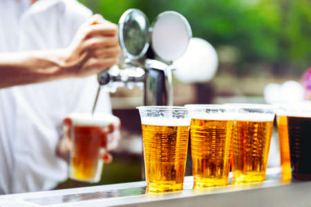 Foto de Man drawing beer from tap in an plastic cup. Draught beer. The bartender pours a beer in a plastic cup. On the bar table are plastic cups with a beer - Imagen libre de derechos