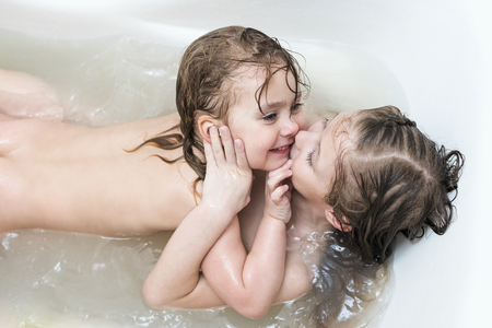 Photo for Two wet sisters laugh and hug lying in the bathroom, close-up - Royalty Free Image