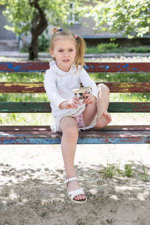 Photo for Beautiful little girl sitting on an old bench shakes the sand out of the flip-flops - Royalty Free Image