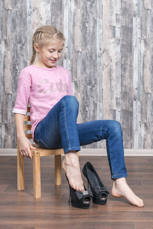 Foto de little beautiful girl sits on a chair and wears black mother high-heeled shoes - Imagen libre de derechos