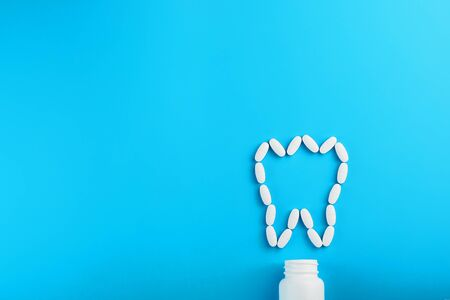 Photo pour White Vitamins with calcium Ca, D3 in the form of a tooth scattered from a white jar on a blue background. The concept of pharmaceuticals and dentistry, dental care. - image libre de droit