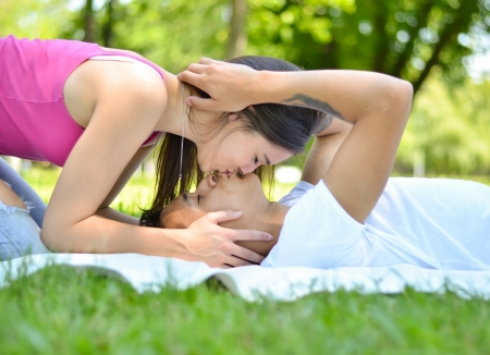 Photo for Happy young couple in park kissing on grass - Royalty Free Image