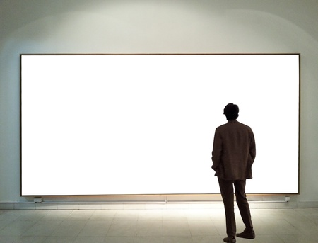Photo for Man in gallery room looking at empty frames - Royalty Free Image