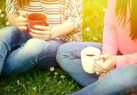Photo pour Young women drinking coffee at park and enjoying summer day - image libre de droit