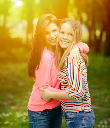 Two young girl friends together in hug at park