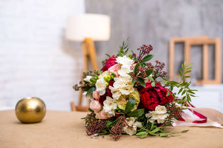 Photo for beautiful modern wedding bouquet on the table. with wedding rings near the bouquet. Against the gray wall. beautiful interior - Royalty Free Image