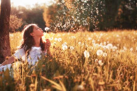 Foto de girl in white dress blow dandelion in outdoor - Imagen libre de derechos