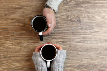 Photo pour two lovers holding each other's hands and drinking coffee at the table - image libre de droit