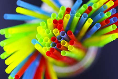 Foto de colored plastic cocktail tubes standing in a glass top view - Imagen libre de derechos