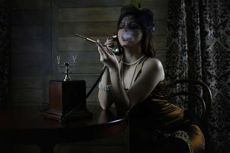 Photo pour Beautiful 1930s girl smokes - image libre de droit